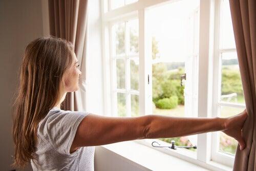 Kobieta otwiera okna A Oczyszczanie energetyczne domu
