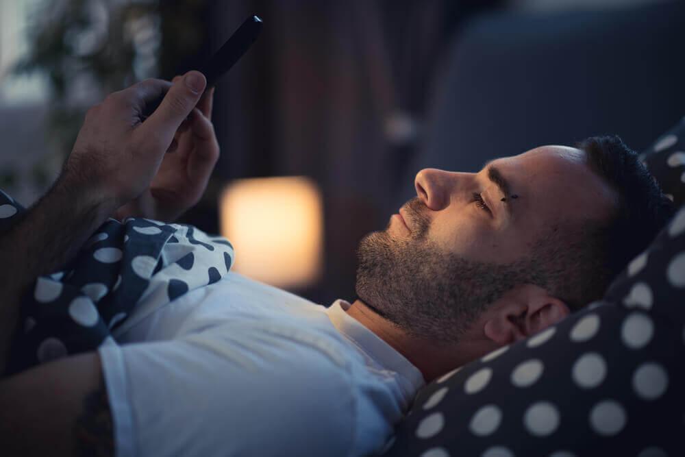 Mężczyzna z telefonem w łóżku - nomofobia