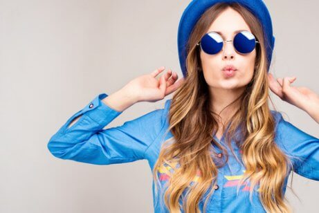 Jasna cera wygląda szczególnie pięknie wśród kontrastowych kolorów, kobieta w niebieskich okularach
