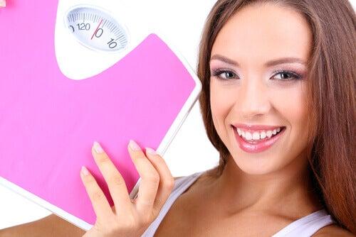 Kobieta trzyma wagę. quinoa w diecie odchudzajacej