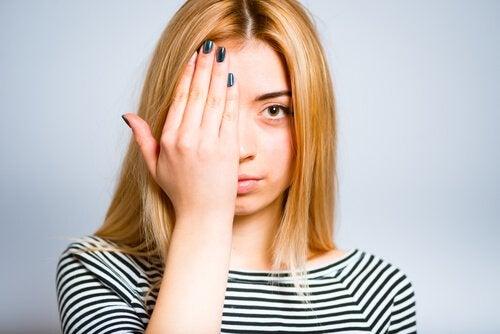 Kobieta zakrywa prawe oko. Białko jaja na zmarszczki na oczach