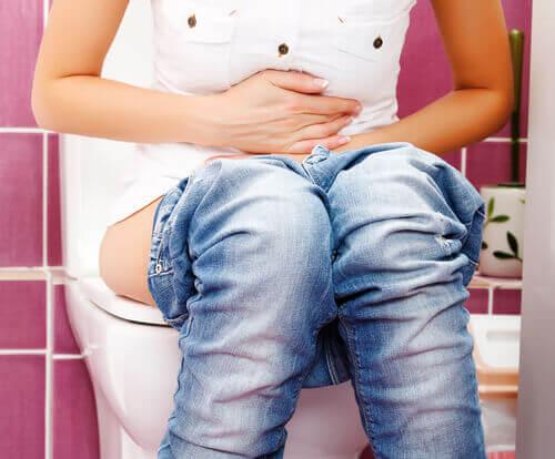 Kobieta na toalecie cierpi na zaparcia a spozywanie Ciepła woda na czczo