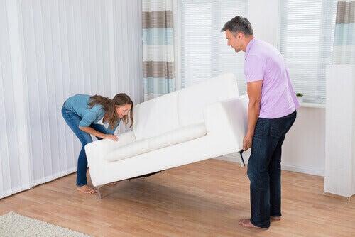 Kobieta z mężem przenosi sofe, porządek w domu