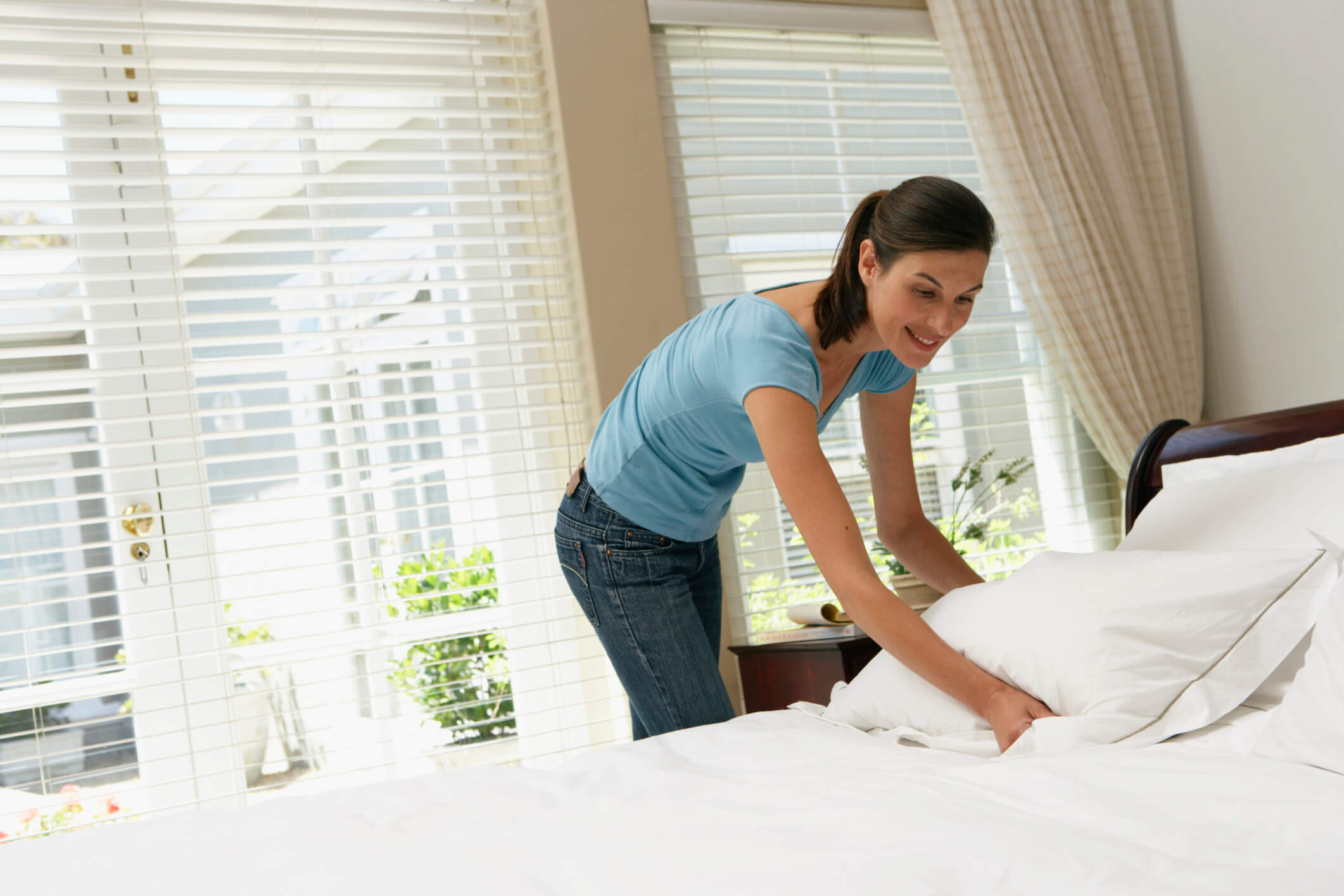 Kobieta ścieląca łóżko