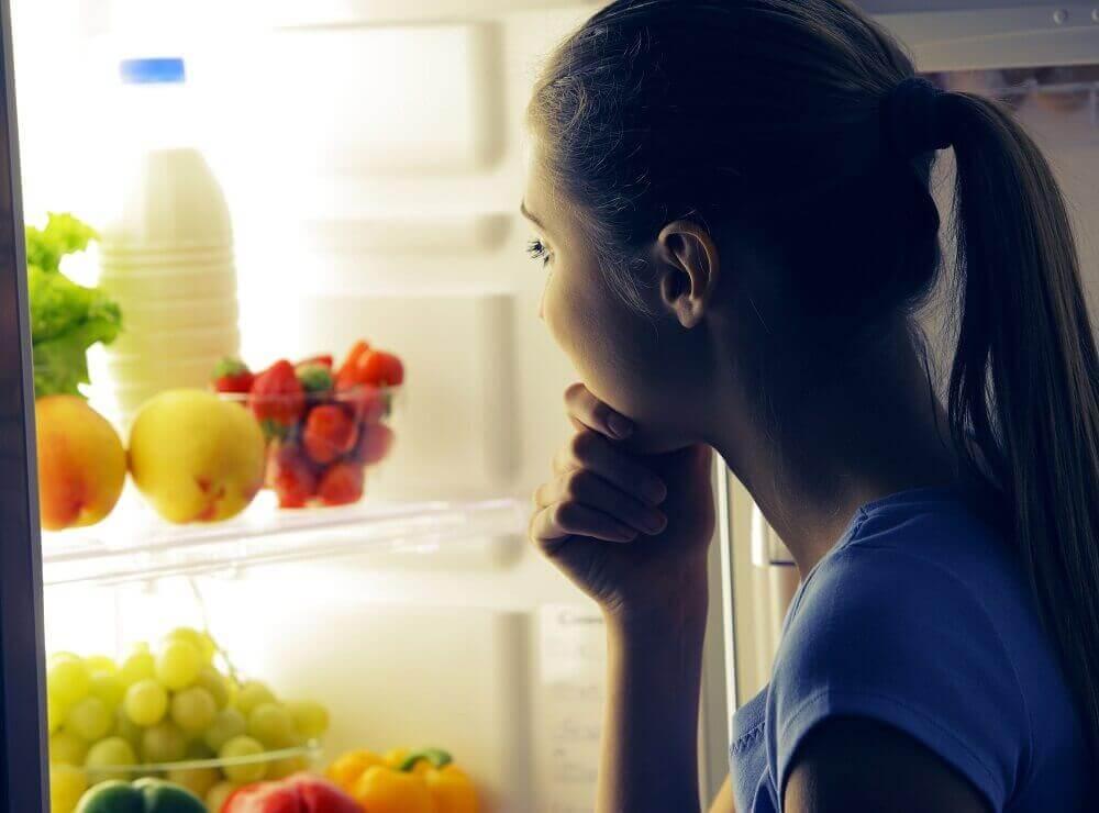bezsenność, kobieta zagląda w nocy do lodówki