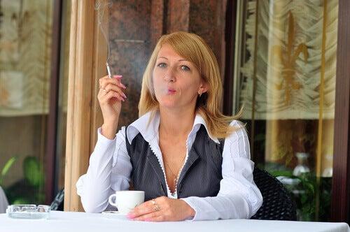 Kobieta pije kawę i pali papierosy.