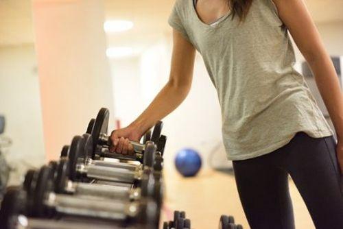 siłownia kobieta podnosi ciężarki, robi trening ciala