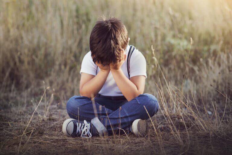 Smutny chłopiec siedzi na ziemi