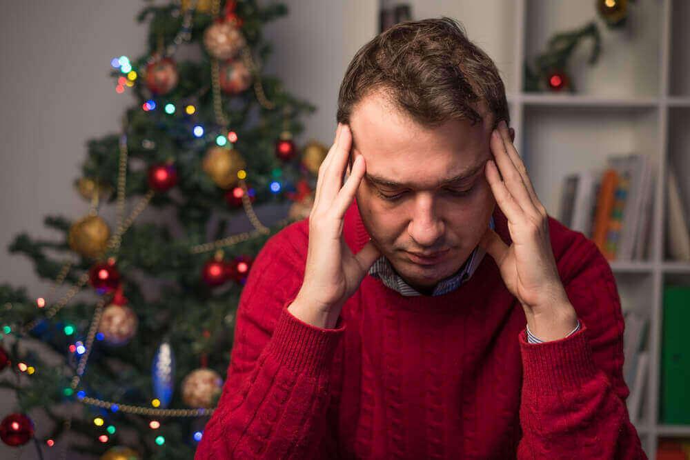 Zmęczony mężczyzna z choinką w tle - nie lubię świąt