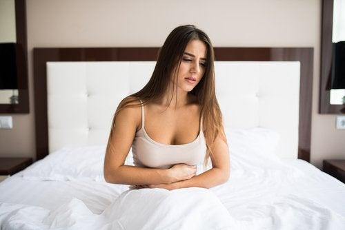Kobieta w łóżku, cierpi na ból brzucha