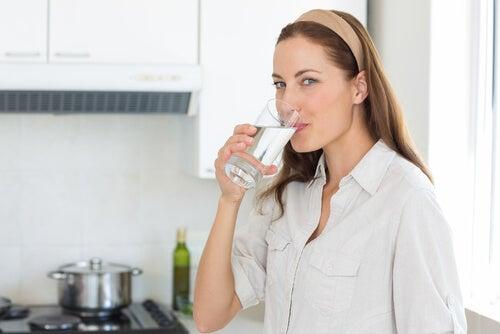 Kobieta pije wodę na niedociśnienie tętnicze