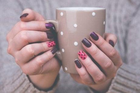 Manicure Zdobienie paznokci, kobieta trzyma kubek