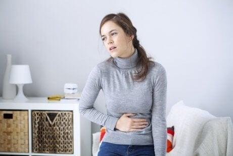 Niestrawność kobieta trzyma się za brzuch a  wrzody żołądka