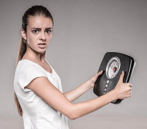 Kobieta trzyma wagę w ręku - wrzody żołądka