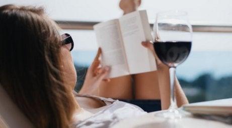 Kobieta czyta książkę przy kieliszku wina