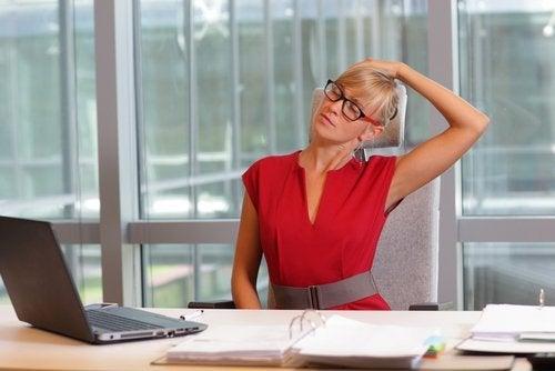Kobieta przy biurku cierpi na ból karku
