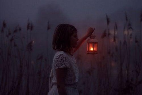 Dziewczynka z latarnią na łące wieczorem