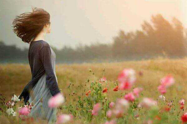 Kobieta spędza czas na łące, aby osiągnąć szczęście