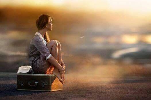 Kobieta siedzi na walizce aby osiągnąć szczęście