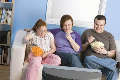 otyłość otyła rodzina na kanapie ogląda telewizję