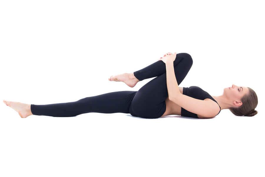 Przyciąganie kolana do klatki piersiowej na wzdęcia i gazy