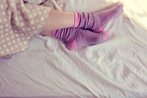 Nogi w skarpetkach i ciepły koc Gdy nie możesz spać,