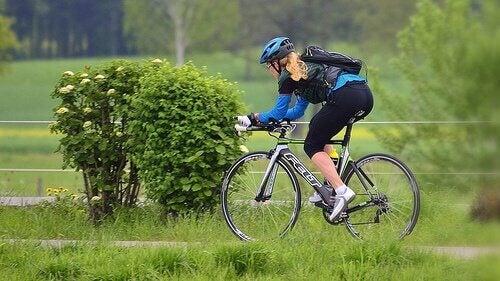 Potas dostarcza energii i uzupełnia płyny i elektrolity, które są tracone gdy się pocimy. kobieta jeździ na rowerze