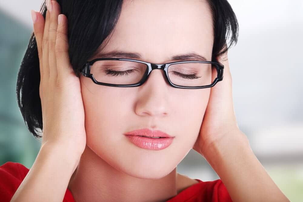 Kobieta zatyka uszy, bo cierpi na szum w uszach