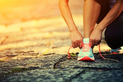 Kobieta zawiązuje buta, trening fibriomialgia