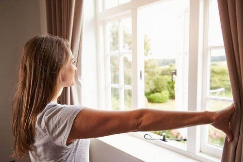 kobieta wygląda przez okno wiosna