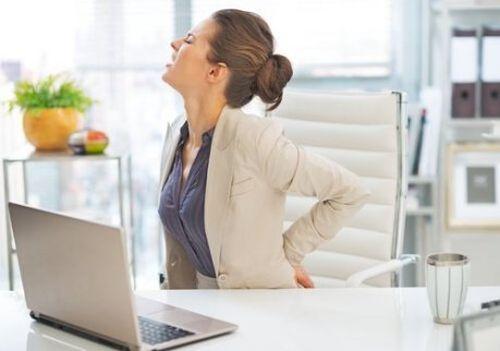 ból pleców u kobiety siedzącej przy biurku
