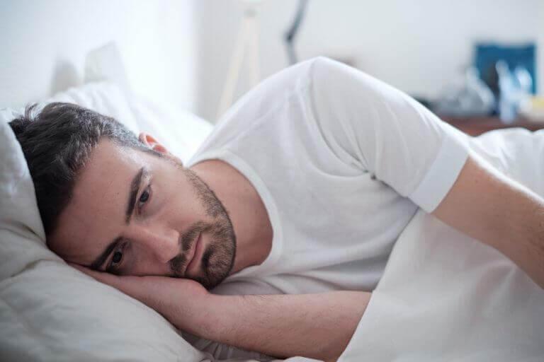 Smutny mężczyzna po rozstaniu rozmyśla w łóżku Poprawa poczucia własnej wartości po rozstaniu zaczyna się od zadbania o siebie
