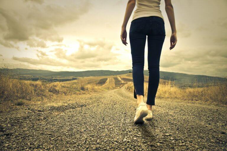 Kobieta spaceruje drogą.