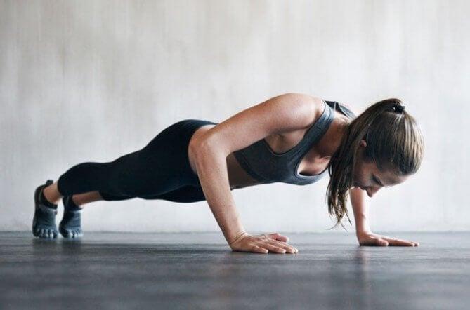 Kobieta robiąca pompki, które pomogą spalić trudny do zredukowania tłuszcz