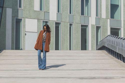 Kobieta schodzi po schodach w dzwonach rozkloszowane dżinsy