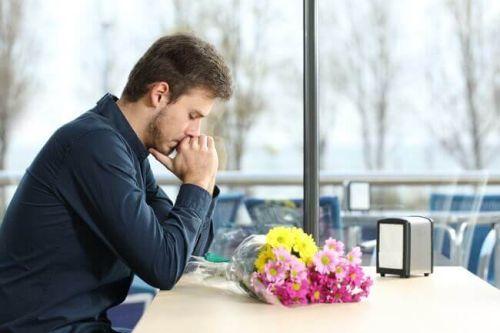 samotny mężczyzna z bukietem kwiatów - wyrzuty sumienia