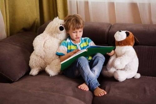 Chłopiec czyta książkę na kanapie