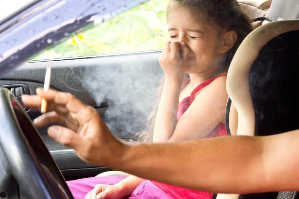 Bierne palenie a rak płuc. Ojciec pali papierosa w aucie przy córce