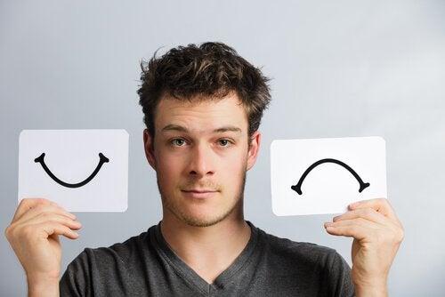 Mężczyzna trzyma kartki uśmiech i smutek - zaburzenie afektywne dwubiegunowe