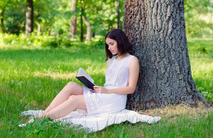 Czytanie książki pod drzewem kobieta