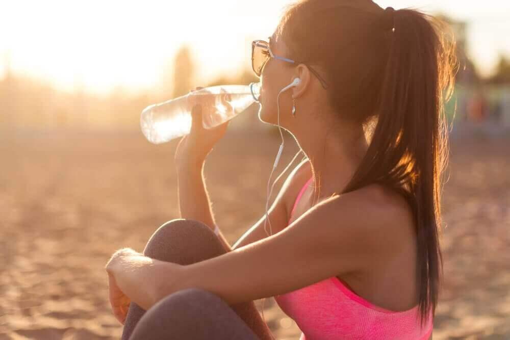 kobieta pije wodę na plaży