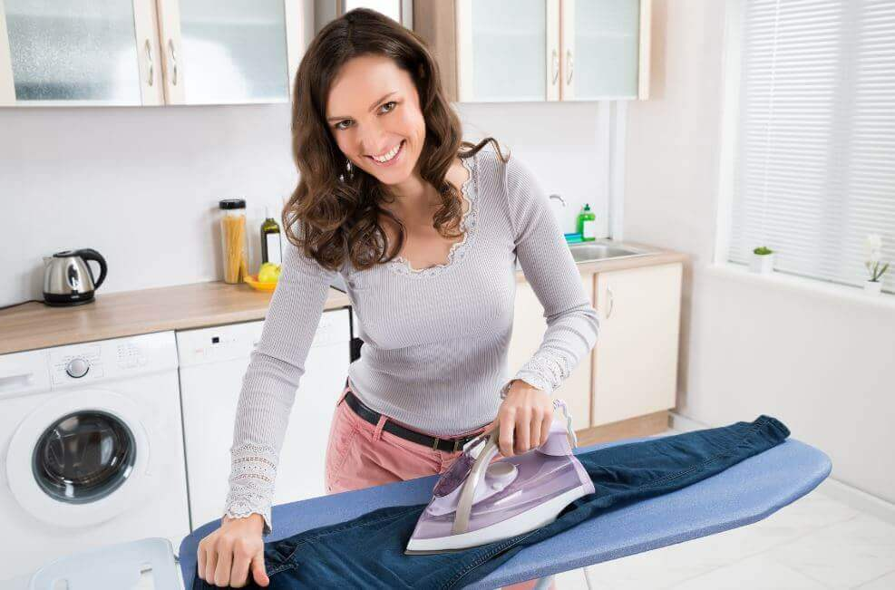 Kobieta prasująca spodnie a folia aluminiowa pod tkaniną ułatwia prasowanie