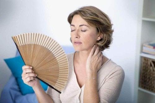 Menopauza - objawy kobieta wachluje się