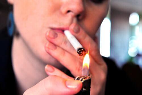 Palenie papierosów a rak płuc kobieta podpala papierosa