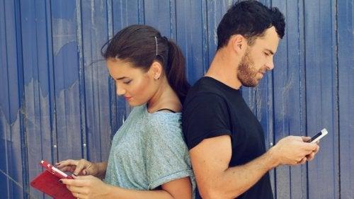 Przyzwyczajenie, kobieta i mężczyzna odwróceni od siebie patrzą na telefony
