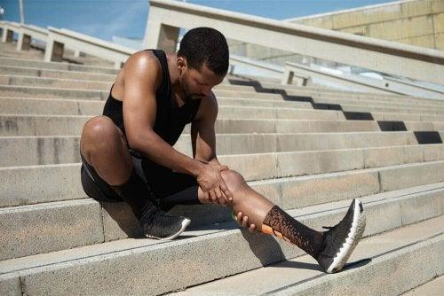sportowiec na schodach rozciąga mięśnie, ucisk łydki skurcz