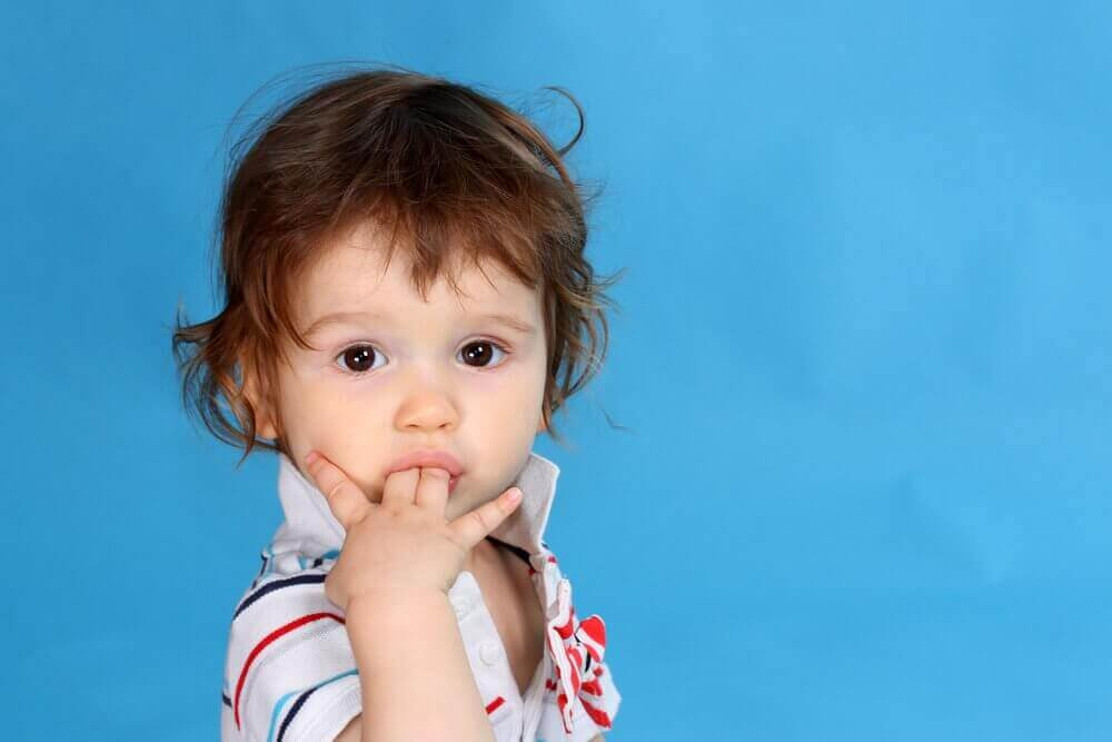Dziecko z palcami w buzi.