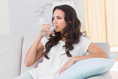 napoje zmniejszające stres, kobieta pije szklankę wody