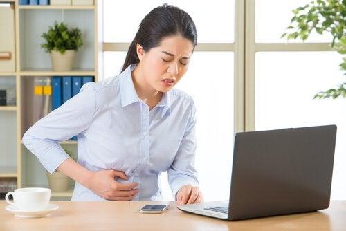 Ból brzucha, kobieta przy biurku cierpi na hemoroidy