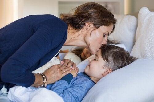 Matka całujaca syna na dobranoc.